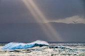 le soleil perce les nuages en éclaire la mer avec des rayons