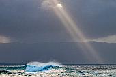 les rayons de soleil traversent les nuages et éclairent la mer