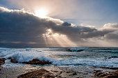 les rayons de soleil traversent les nuages et éclairent la mer sur le littoral Corse