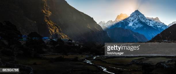Rays of light illuminating mountain valley Sherpa villge Himalayas Nepal