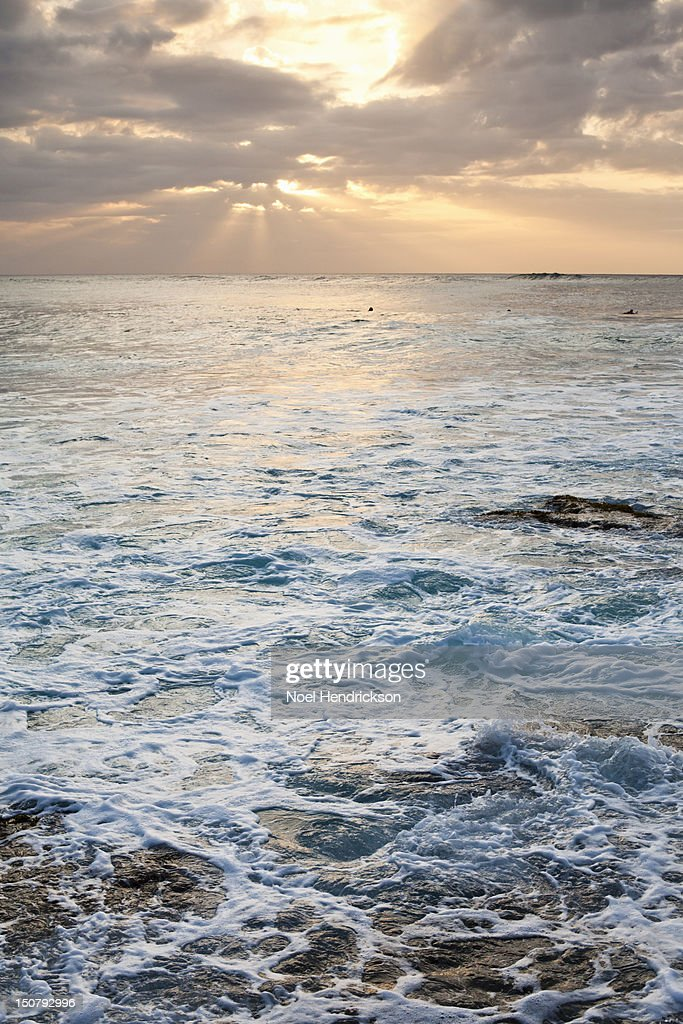 Rays of sun shine through clouds over the ocean : Stock Photo