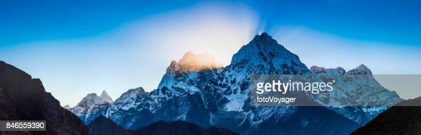 Rays of sunlight beaming through Kangtega Thamserku Himalaya mountains Nepal