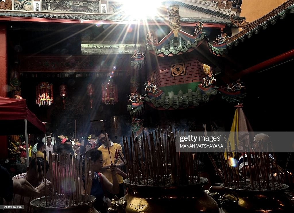 Rays of sunlight fall on ethnic Malaysian-Chinese devotees at the Guan-Di Temple on the first day of the Lunar New Year in Kuala Lumpur's popular Chinatown area on February 8, 2016. Some 25 percent of Malaysia's 29 million people are ethnic Chinese and celebrate the Lunar New Year, this year marking the Year of the Monkey. AFP PHOTO / MANAN VATSYAYANA / AFP / MANAN VATSYAYANA