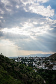 Rays of sunlight in the afternoon filtered through storm clouds lightning the city of Granada