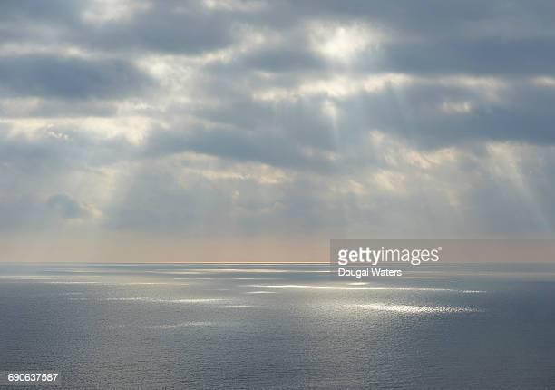 Rays of sunlight over vast seascape.