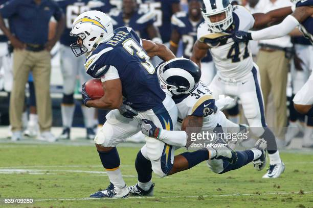 Rayshawn Jenkins of the Los Angeles Chargers breaks a tackle before being brought down by Aarion Penton of the Los Angeles Rams during the preseason...