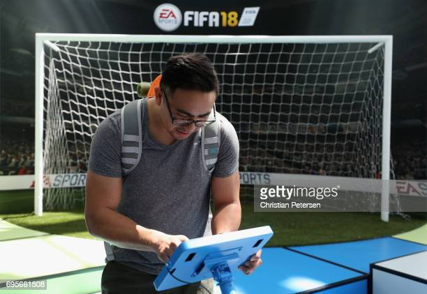 Rayson Esquejo participates in a Fifa 18 booth during the Electronic Entertainment Expo E3 at the Los Angeles Convention Center on June 13 2017 in...