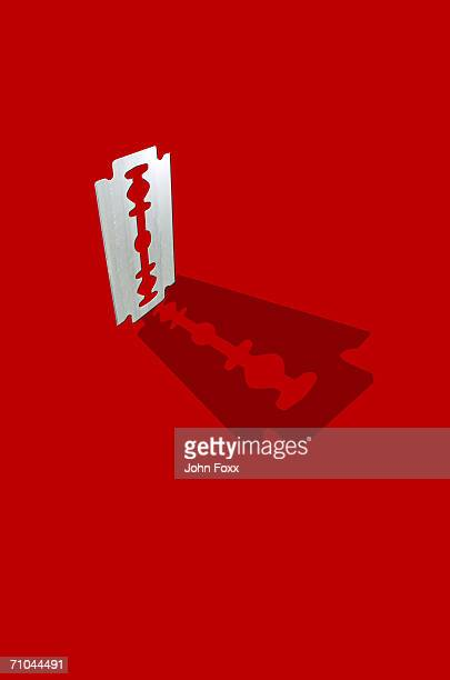 Razor blade on red background, close-up