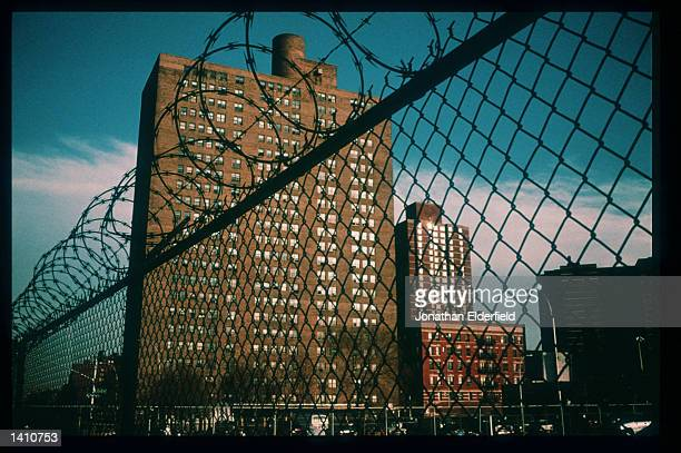 A razor wire fence stands near a housing project in the East Village June 1 1998 in New York City Populated by residents of numerous heritages...