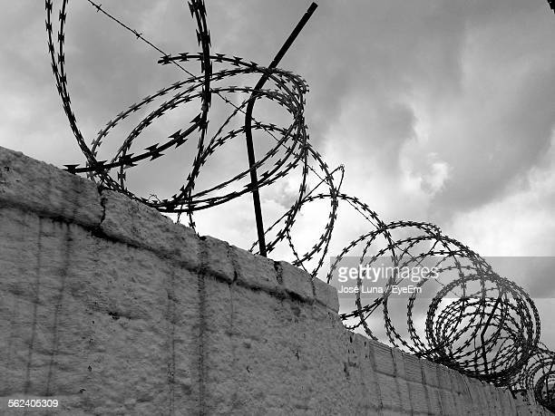 Razor Wire Fencing On Wall Against Cloudy Sky
