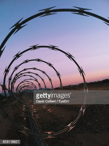 Razor Wire On Chainlink Fence Against Clear Sky