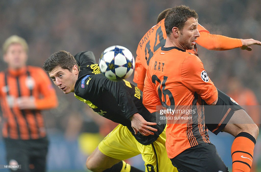 Razvan Rat (R) of FC Shakhtar fights for a ball with Robert Lewandowski (L) of Borussia Dortmund during UEFA Champions League, Round 16, football match in Donetsk on February 13, 2013. AFP PHOTO/ SERGEI SUPINSKY