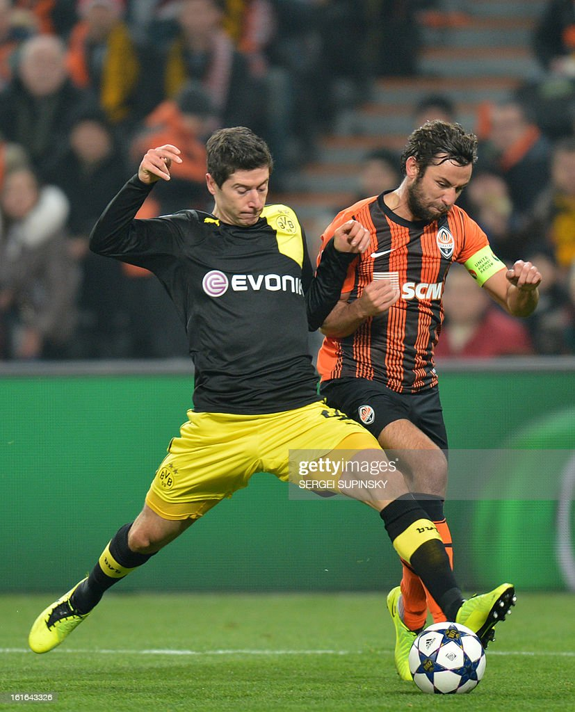 Razvan Rat (R) of FC Shakhtar fights for a ball with Robert Lewandowski of Borussia Dortmund during UEFA Champions League, Round 16, football match in Donetsk on February 13, 2013.