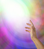 Open hand reaching up towards a ball of white light on a multicolored background
