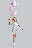 Full length studio shot of playful young woman holding balloons and smiling while jumping against grey background