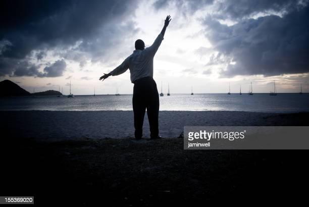Raggiungendo verso il cielo; uomo silhouette al tramonto, vicino alla spiaggia