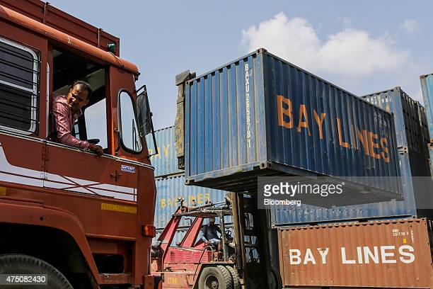 A reachstacker moves a Freight Connection India Pvt Bay Lines branded shipping container as a truck reverses at Five Star Marine Services freight...