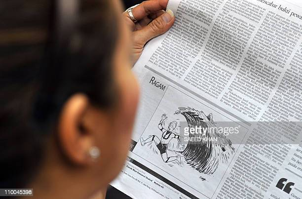 A reader looks at the page of a newspaper with a cartoon depicting the popular Japanese icon Ultraman running away from a tsunami wave in Kuala...