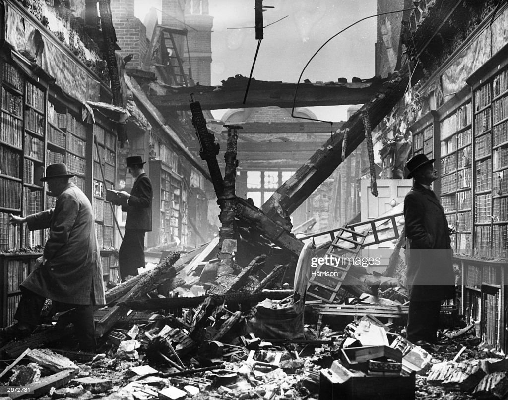 Readers choosing books which are still intact among the charred timbers of the Holland House library, London.