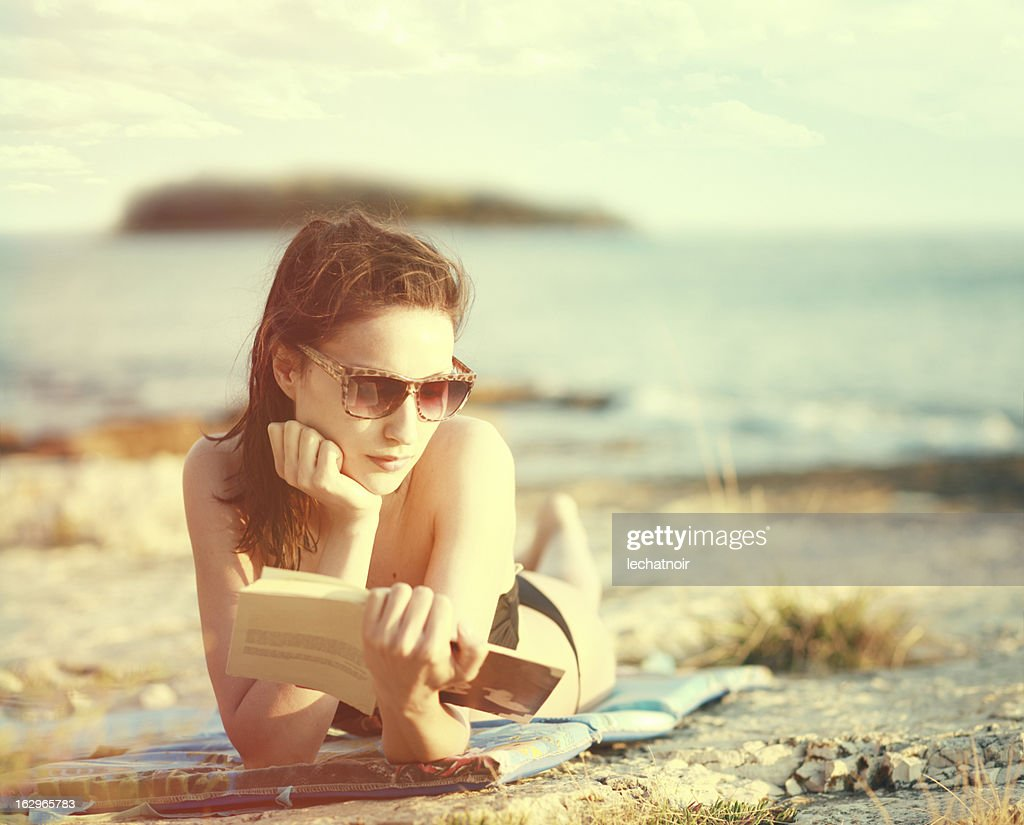 Reading a book on the sunny beach