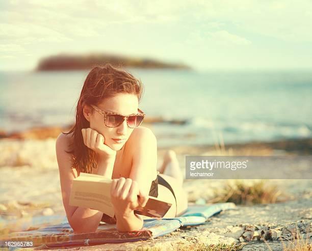 La lettura di un libro sulla soleggiata spiaggia