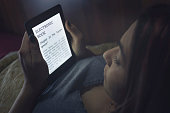 During the night, a girl is reading an ebook with her backlit ereader device while she's in bed. Note: Lorem Ipsum text there are no copyright issues