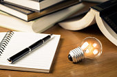 Small light bulb glowing on the desk, with notebook and many books on background, reading and writing idea concept