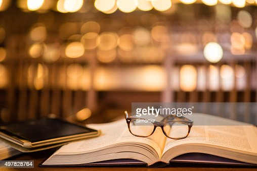 Reading glasses and digital tablet on book