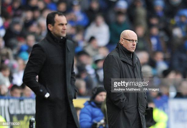 Reading manager Brian McDermott is seen beyond Wigan Athletic manager Roberto Martinez as they stand on the touchline