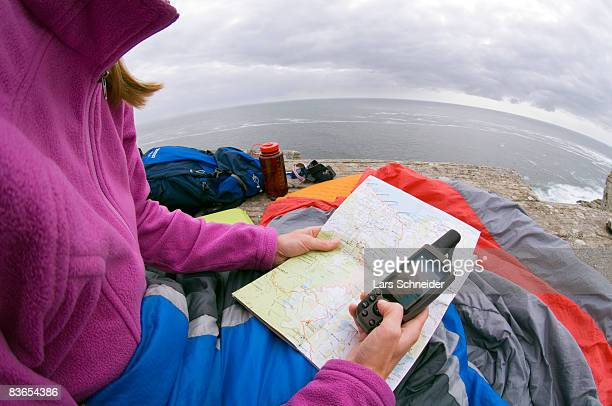 Reading map & GPS at camp on rocky ocean cliff.