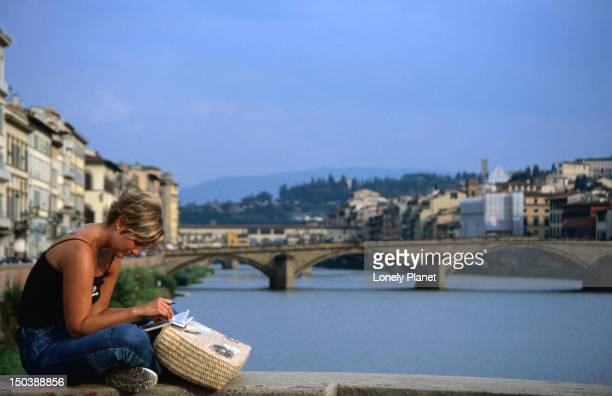 Reading surrounded by the Arno and the Ponte Vecchio and Ponte Santa Trinita of Florence.