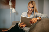 Attractive young woman sitting on a sofa holding a tablet