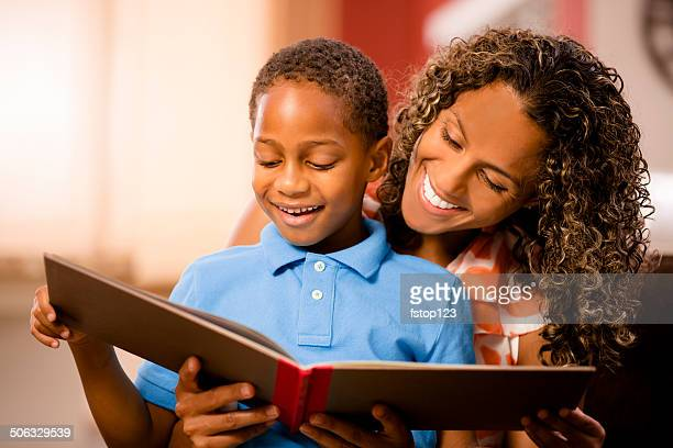 Reading with mom! African descent mother, child and book. Home.