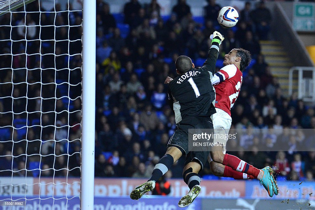 "Reading's Australian goalkeeper Adam Federici (L) clears the ball under pressure from Arsenal's Moroccan striker Marouane Chamakh (R) during extra time in the English League Cup Fourth Round football match between Reading and Arsenal at The Madejski Stadium, in Reading, England on October 30, 2012. Arsenal won the game 7-5 after extra time. USE. No use with unauthorized audio, video, data, fixture lists, club/league logos or ""live"" services. Online in-match use limited to 45 images, no video emulation. No use in betting, games or single club/league/player publications"