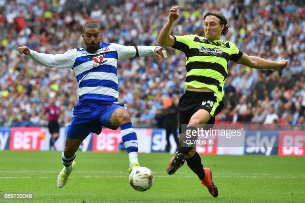 TOPSHOT Reading's English striker Lewis Grabban vies with Huddersfield Town's German defender Michael Hefele during the English Championship playoff...