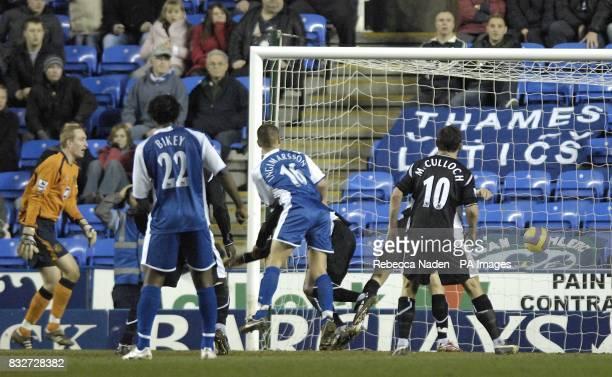 Reading's Ivar Ingimarsson scores the equalizer as Wigan Athletic's goalkeeper Chris Kirkland looks on