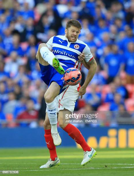 Reading's Jamie Mackie controls the ball in the air despite the challenge of Arsenal's Laurent Koscielny