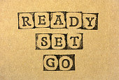 Words Ready Set Go make by black alphabet stamps on cardboard.