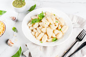 Italian food recipe, Healthy vegan dinner with potato gnocchi. With grated parmesan cheese, basil and pesto sauce. On white marble , copy space