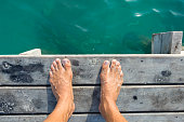 High angle POV of man's bare feet standing at edge of wooden dock sprinkled with fine white sand above aqua green sea water in natural morning light