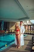 Shot of a young couple standing by the pool