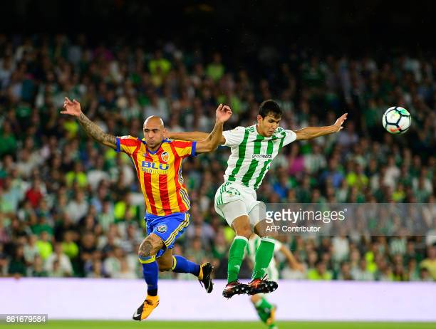 Real Betis' Algerian defender Aissa Mandi jumps for the ball with Valencia's Italian forward Simone Zaza during the Spanish league football match...