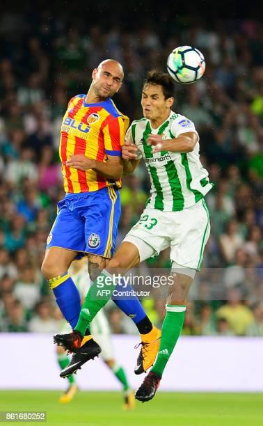 Real Betis' defender from Algeria Aissa Mandi jumps for the ball with Valencia's forward from Italy Simone Zaza during the Spanish league football...