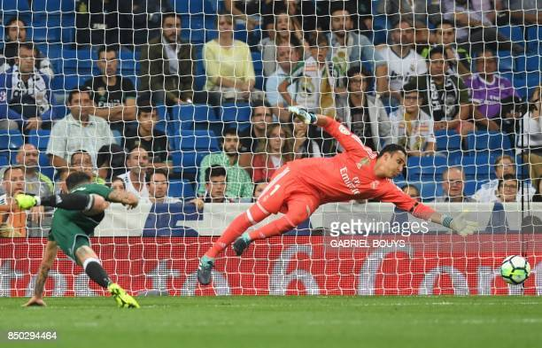 Real Betis' forward from Paraguay Arnaldo Sanabria heads the ball in front of Real Madrid's goalkeeper from Costa Rica Keylor Navas to score a goal...