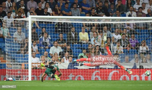 Real Betis' forward from Paraguay Arnaldo Sanabria heads the ball to score a goal as Real Madrid's goalkeeper from Costa Rica Keylor Navas dives for...