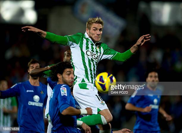 Real Betis' French defender Damien Perquis vies with Getafe's defender Miguel Torres during the Spanish league football match Getafe vs Real Betis at...