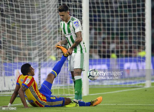 Real Betis' Paraguayan forward Arnaldo Sanabria helps Valencia's Colombian defender Jeison Murillo during the Spanish league football match Real...