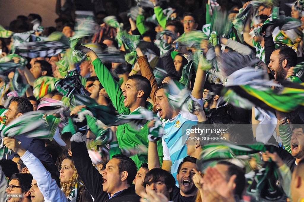 Real Betis' supporters cheer and wave scarves during the Europa League football match Real Betis Balompie vs Sevilla FC at the Benito Villamarin...