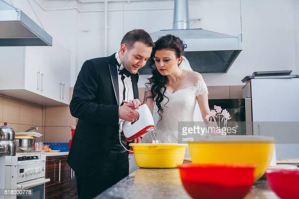 Real sposo e sposa cottura torta nuziale in cucina