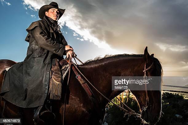 Real Cowboys: Man riding bay horse along ranch trail.